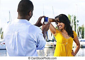 Woman posing for picture near boats