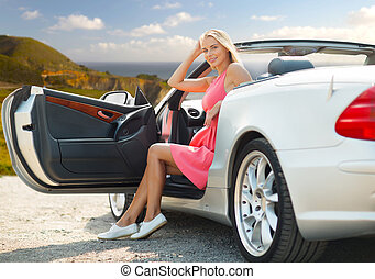 woman posing in convertible car at big sur coast