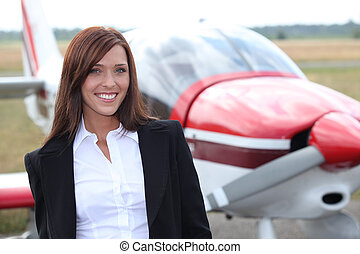 Woman posing in front of airplane