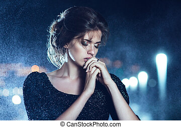 Woman posing in the rain. - Beautiful woman in black dress...
