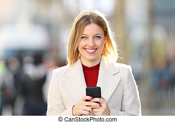 Woman posing looking at you holding a smart phone