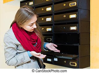 Woman posing near empty mailbox