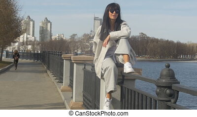 Woman posing on fence of waterfront
