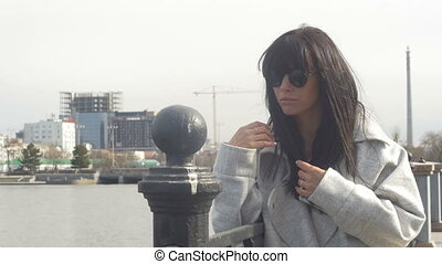 Woman posing on waterfront - Young woman wearing sunglasses...