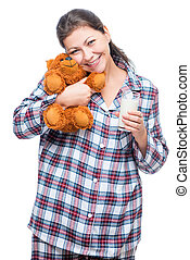 Woman posing on white background in pajamas with toy and a glass of milk