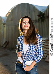 Woman posing outdoors, greenhouse buildings on background