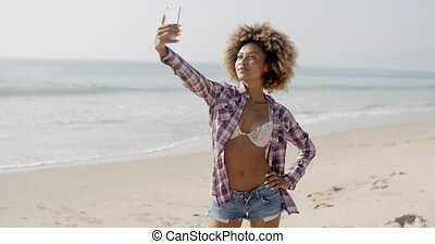 Woman Posing To Take A Selfie On The Beach