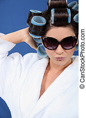 Woman posing wearing sunglasses and hair rollers