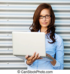 Woman posing while holding the laptop