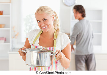 Woman posing with a boiler while her fiance is washing the dishes in their kitchen