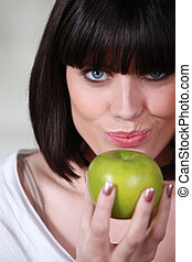 Woman posing with a green apple