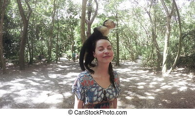 Woman posing with a monkey on her head. - Woman posing for a...