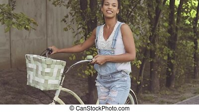 Woman posing with bicycle at street
