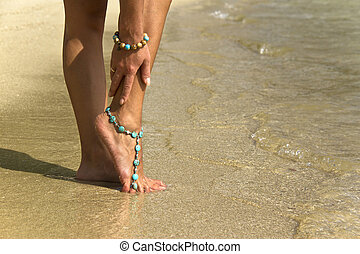 Woman posing with bracelets in surfing waves