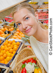 woman posing with fruits in the background