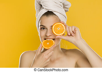 woman posing with orange on yellow background