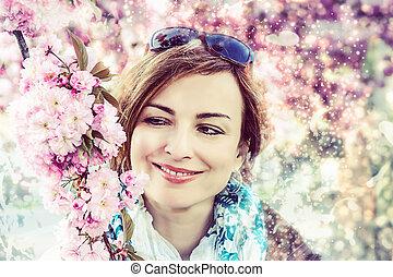 Woman posing with sakura tree, photo filter