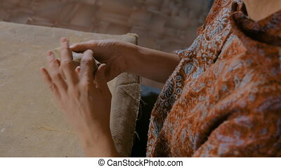 Woman potter making ceramic souvenir penny whistle in pottery workshop