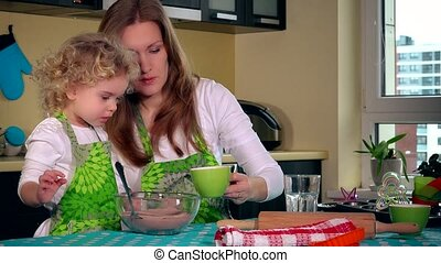 Woman pour oil into cake dough and little helper daughter girl mixing with spoon