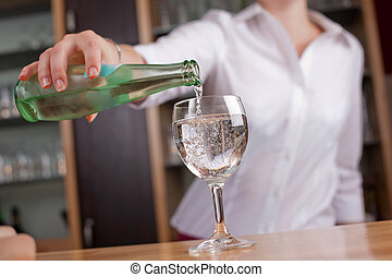 Woman pouring a glass of mineral water
