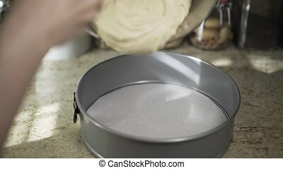 Woman pouring dough to a form