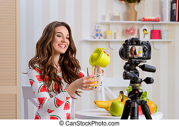 Woman pouring fresh juice into a glass from a juicer