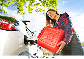 Woman pouring fuel into gas tank of a car from can