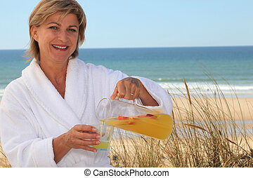 Woman pouring herself a glass of orange juice at the beach