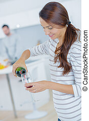 Woman pouring herself a glass of red wine