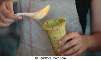Woman pouring hot vegetable soup into baked cone