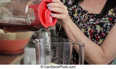 Woman pouring juice in the blender