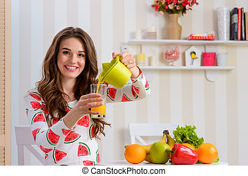 Woman pouring juice into a glass from a juicer
