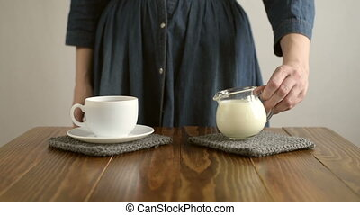 Woman pouring milk into a cup of coffee
