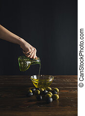 woman pouring oil from bottle to bowl