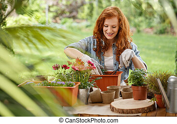 Woman pouring soil into container