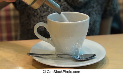 Woman pouring sugar into the cup of tea