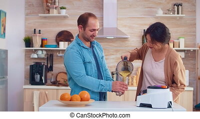 Woman pouring tasty smoothie from blender in glasses for her and husband. Cheerful family making together organic healthy fresh nutritious tasty juice for breakfast from fresh fruits while on a diet.