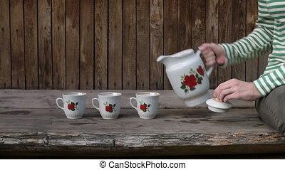 Woman pouring tea into three mugs