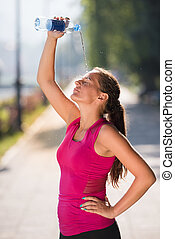 woman pouring water from bottle on her head