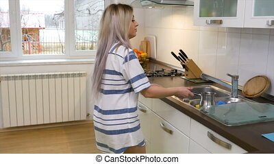 Woman pouring water in a kettle and preparing coffee in the morning at home
