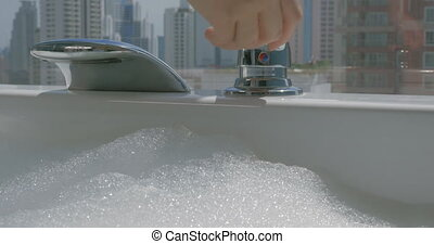 Woman pouring water into the bathtub with foam