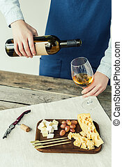 woman pouring white wine into glass