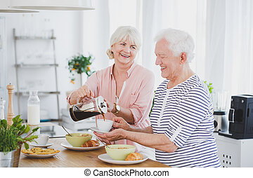 Woman pours coffee into the cup