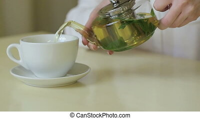 woman pours green tea from teapot