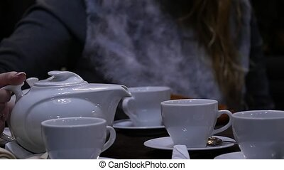 Woman pours herbal tea in a white cup in cafee. slow motion...