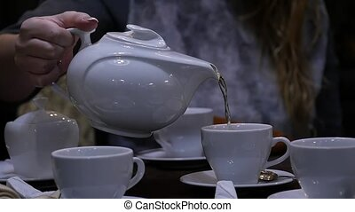 Woman pours herbal tea in a white mug in cafee. slow motion.