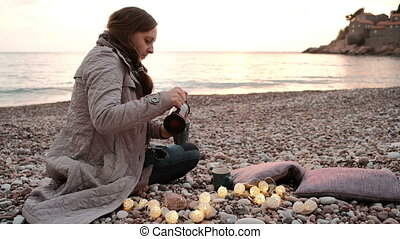 Woman pours hot tea in a cup and admiring the sunset on the beach.
