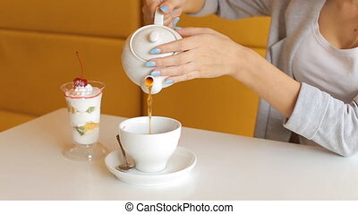 woman pours hot water from the kettle into the cup