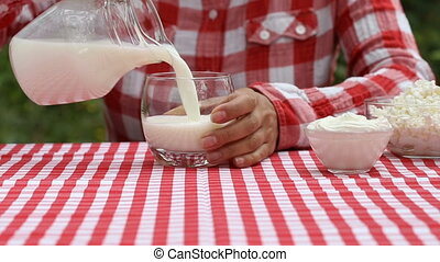 Woman pours milk into glass from jug and hands it to her