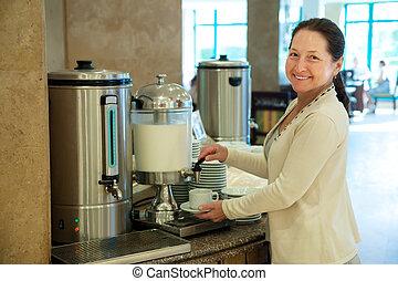Woman pours milk to coffee